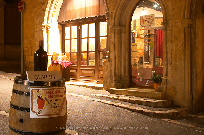 A cobble stone street in the old town with a wine shop. At night. a wine barrel on the street advertising Beaujolais Nouveau, Cave Le Temps du Vin, rue des Fontaines Bergerac Dordogne France