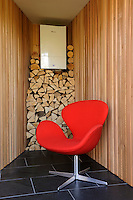 A classic Arne Jacobsen Swan chair upholstered in a vibrant red orange stands out against the cedar clad walls and Brazilian black slate flooring.