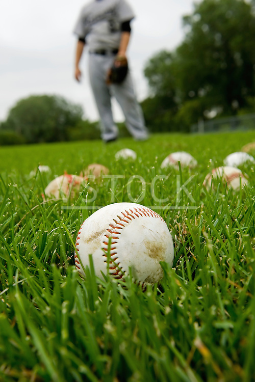 USA, Minnesota, Roseville, baseballs in grass, defocused man in background