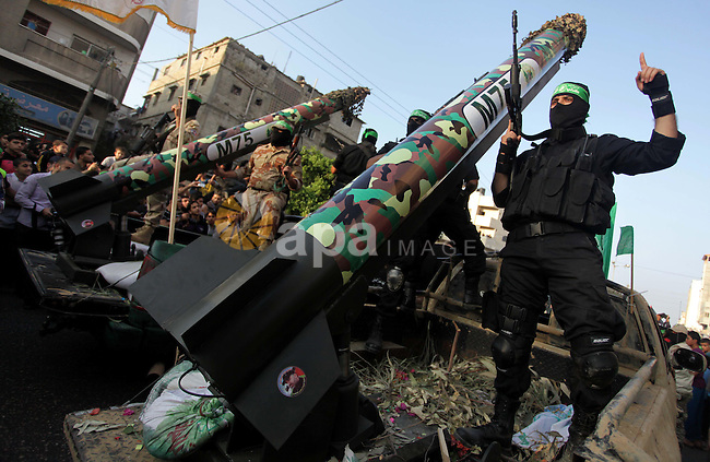 Palestinian militants of the Ezzedine al-Qassam Brigades, Hamas's armed wing, stage an anti-Israel parade as part of the celebrations marking the first anniversary of an Israeli army operation in Gaza, on November 14, 2013. A year after trading fire in a week-long war in Gaza, in which more than 170 Palestinians and six Israelis were killed, Israel and Hamas are squaring up for another confrontation, despite both sides appearing reluctant to make the first move. Photo by Ashraf Amra