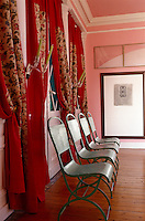 A simple row of metal chairs highlights the deep red and chintz curtains against the pink walls of the dining room