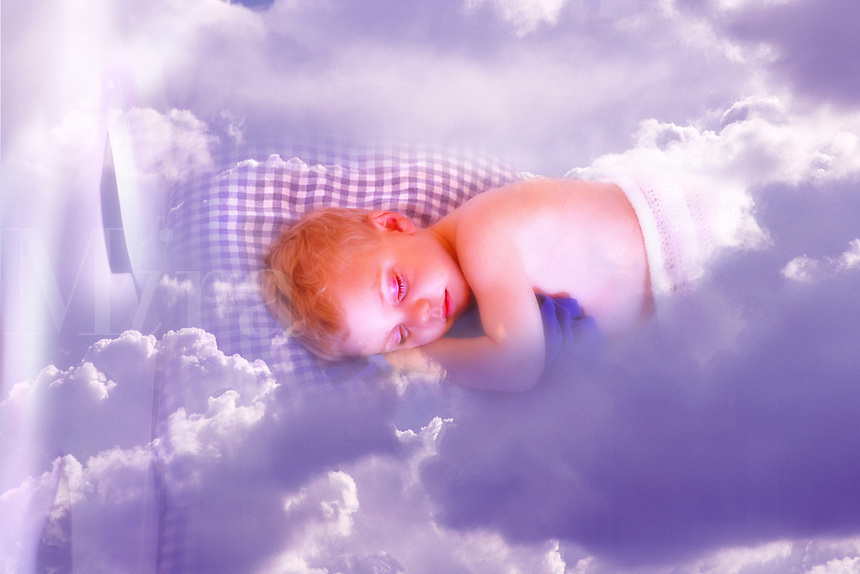 Child sleeping in white bed with blue check sheets among clouds