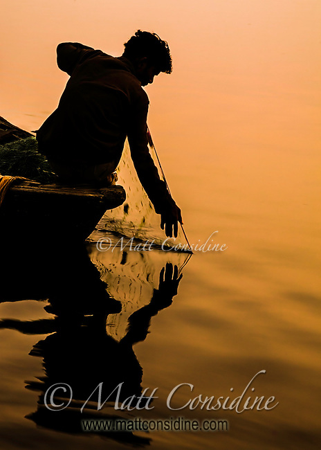 Fisherman drags in his net in the dawn light..(Photo by Matt Considine - Travel Photographer)