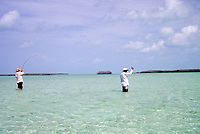Fly fishing guide and angler hooked up to a bonefish, Albula vulpes. Cayo Largo, Cuba