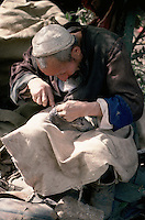 The weekly Sunday market in Kashgar, in the far-west Xinjiang province of China, attracts thousands of traders and customers from a huge surrounding area. This aged cobbler has set up his stall for the day and sits mending shoes.