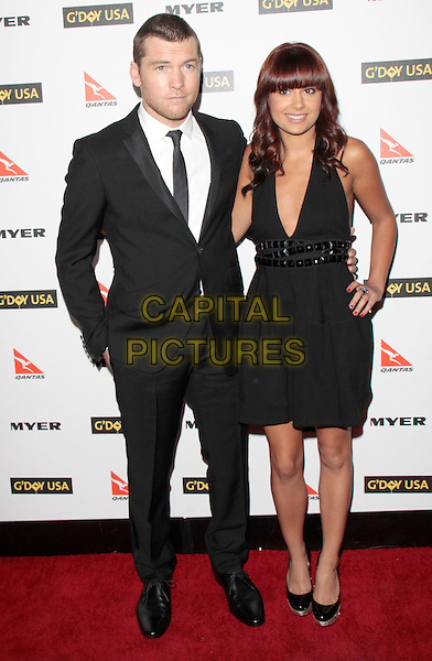 SAM WORTHINGTON & NATALIE MARK.Attending the 2010 G'Day USA Australia Week Black Tie Gala held at the Hollywood & Highland Grand Ballroom, Hollywood, California, USA, .16th January 2010. .arrivals full length black suit tie dress hand in pocket on hip couple patent shoes platform studs studded low cut .CAP/RKE/DVS .©DVS/RockinExposures/Capital Pictures