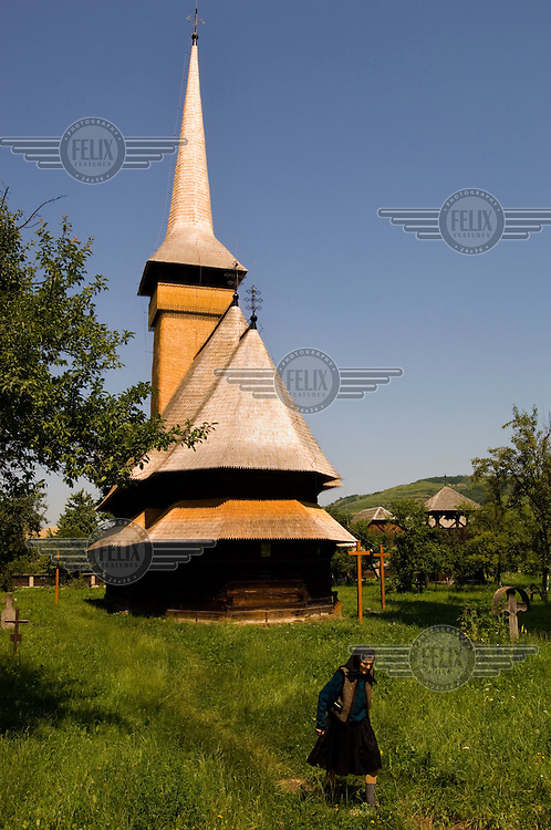 A woman walks in front of the wooden church at Bogdan Voda.