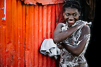 A Haitian girl bathes outside her sheet-metal house in a shanty town close to La Saline market, Port-au-Prince, Haiti, 14 July 2008. Although Latin America (as a whole) is blessed with an abundance of fresh water, having 20% of global water resources in the the Amazon Basin and the highest annual rainfall of any region in the world, an estimated 50-70 million Latin Americans (one-tenth of the continent's population) lack access to safe water and 100 million people have no access to any safe sanitation. Complicated geographical conditions (mainly on the Pacific coast), unregulated industrialization (causing environmental pollution) and massive urban poverty, combined with deep social inequality, have caused a severe water supply shortage in many Latin American regions.