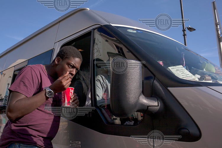 A man with a cup of Coca-Cola in his hand checks himself in a van's mirror.
