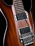 Artistic closeup photo of electric guitar natural brown wood color