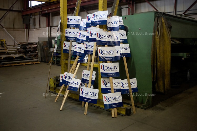 Mitt Romney campaign signs rest in the background of a Romney campaign event to begin at Gilchrist Metal Fabricating in Hudson, New Hampshire, on Jan. 9, 2012.  Romney is seeking the 2012 Republican presidential nomination.