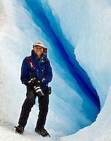 A photographer posing with a crevasse of blue ice on Glacier Perito Moreno in Parque Nacional los Glaciares, Argentina.