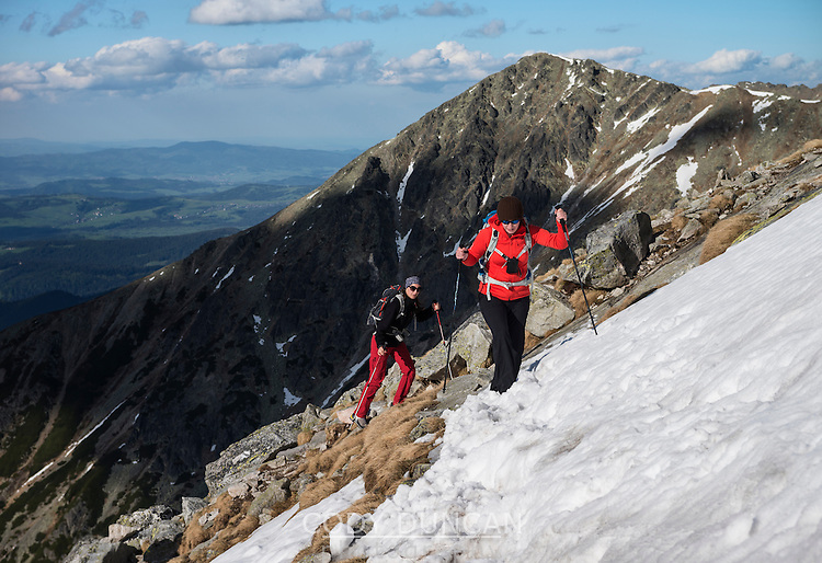 Two Female hikers cross snow near summit of Koscielec (2155m), Tatra mountains, Poland
