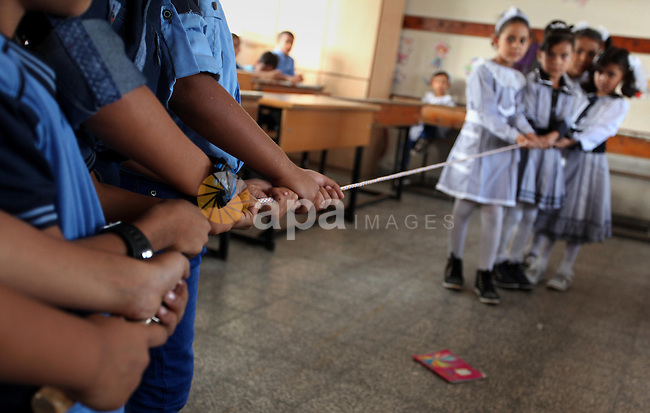 Palestinian schoolchildren play a game in a classroom on the first day of a new school year, at a United Nations-run school in Khan Younis in the southern Gaza Strip August 28, 2016. Photo by Ashraf Amra