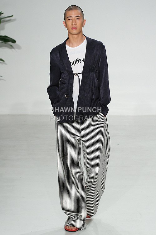 Model walks runway in a navy spanish silk double tie noragi, Gorbachev tee, and Japanese stripe wide leg trouser, from the Palmiers du Mal Spring Summer 2017 collection by Brandon Capps and Shane Fonner, at Skylight Clarkson Square on July 14 2016, during New York Fashion Week Men's Spring Summer 2017.