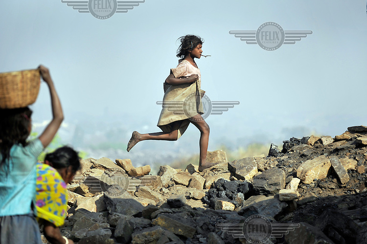 A girl chews on a twig as she runs through the rubble of an open cast mine. Many villagers survive by selling coal that has been illegally collected.