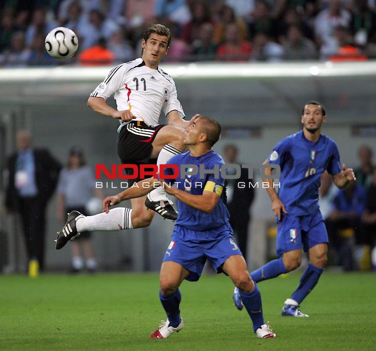 FIFA WM 2006 -  Semi Finals / Halbfinale<br /> Play    #61 (04-Juli) - Deutschland - Italien<br /> <br /> Miroslav Klose (links) von Deutschland im Zweikampf mit Fabio Cannavaro (Mitte) von Italien.<br /> <br /> Foto &copy; nordphoto