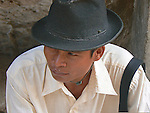 A young man sits and waits in the shade,  wearing a rather dapper hat.