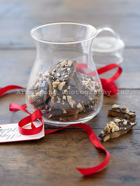 A glass container of toffee with nuts and chocolate, with a ribbon and tag that reads  'Happy Holidays'