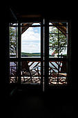 Eagle Bay, New York. Big Moose Lake. The Waldheim (vacation resort in the style of the traditional Adirondack great camps).  View from unit named The Loft looking outside to the porch and the lake. ID: AJ-DC. © Ellen B. Senisi
