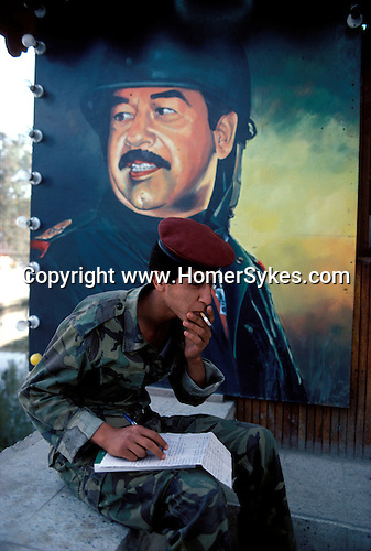 Marsh Arabs. Southern Iraq. Circa 1985.  Marsh Arab young soldier, Basrash - soldier smoking, in front of poster of Saddam Hussein in military uniform