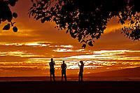 Fishing at sunset while standing on the breakwater at Magic Island in Ala Moana Beach Park, Honolulu, O'ahu.