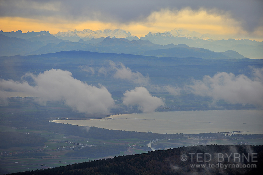 Swiss Alps as seen from Chasseral summit on an overcast day in golden light