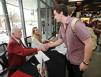 "STAFF PHOTO ANDY SHUPE - Jackson Goodman, a sophomore at the University of Arkansas from Fayetteville, right, shakes the hand of Frank Broyles, former coach and director of athletics at the university, Friday, Dec. 12, 2014, as Broyles' granddaughter Molly Arnold Gay assists after Goodman had a copy of the book, ""An Arkansas Legend: The Life & Legacy of Frank Broyles,"" autographed during a book signing at the University Bookstore on the University of Arkansas campus in Fayetteville. Ten percent of book sale proceeds will be donated to the Frank and Barbara Broyles Foundation: Care Givers United for Alzheimer's and Dementia. Broyes, 89, will take part in another event to sign limited-edition footballs celebrating the 50th anniversary of the 1964 National Championship season Wednesday at 2:30 p.m. at the Bank of Fayetteville with all proceeds benefitting the foundation."