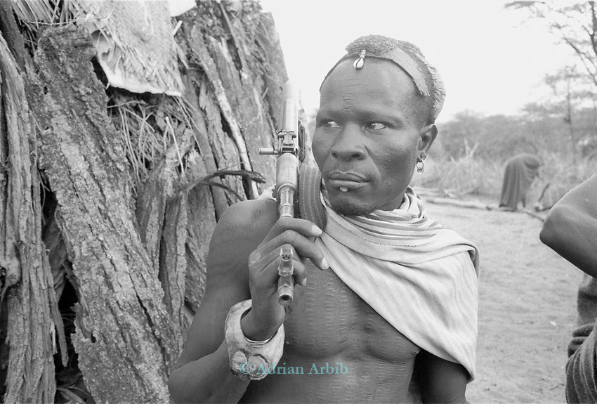 A Turkana fighter and automatic weapon in a traditional village nr Kakuma, Northern Kenya.<br /> His family may use the gun as protection against marauding tribes that come and steal their livestock.<br /> <br /> With the high amount of unrest in the region there has been a proliferaiton of weapons and a Kalashnikov can be  bought for as little as $10 USD.