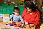 Education Preschool 3-5 year olds female teacher working with girl on patterns, colors, and counting horizontal