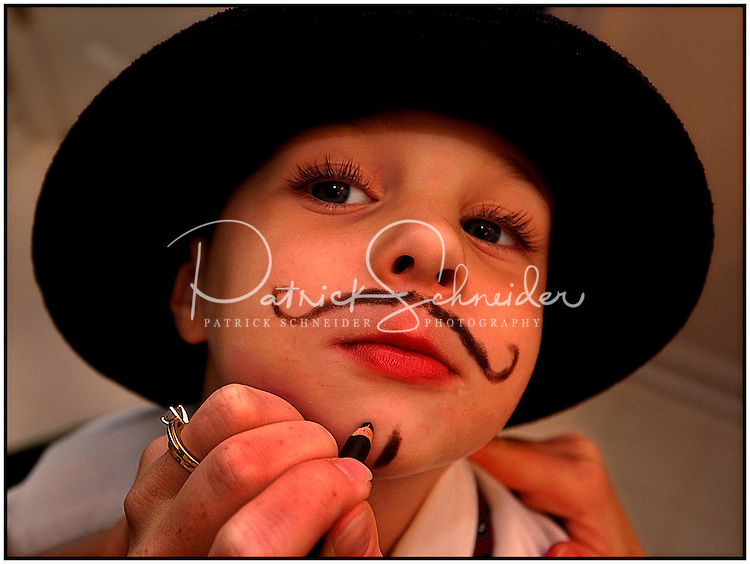 A boy, playing dress up, has his face drawn on. Model release.