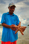 A man show a sea star he collected in the village of Hessessai Bay at PanaTinai (Panatinane)island in the Louisiade Archipelago in Milne Bay Province, Papua New Guinea.  The island has an area of 78 km2..The Louisiade Archipelago is a string of ten larger volcanic islands frequently fringed by coral reefs, and 90 smaller coral islands located 200 km southeast of New Guinea, stretching over more than 160 km and spread over an ocean area of 26,000 km? between the Solomon Sea to the north and the Coral Sea to the south. The aggregate land area of the islands is about 1,790 km? (690 square miles), with Vanatinai (formerly Sudest or Tagula as named by European claimants on Western maps) being the largest..Sideia Island and Basilaki Island lie closest to New Guinea, while Misima, Vanatinai, and Rossel islands lie further east..The archipelago is divided into the Local Level Government (LLG) areas Louisiade Rural (western part, with Misima), and Yaleyamba (western part, with Rossell and Tagula islands. The LLG areas are part of Samarai-Murua District district of Milne Bay. The seat of the Louisiade Rural LLG is Bwagaoia on Misima Island, the population center of the archipelago.PanaTinai (Panatinane) is an island in the Louisiade Archipelago in Milne Bay Province, Papua New Guinea. The island has an area of 78 km2..The Louisiade Archipelago is a string of ten larger volcanic islands frequently fringed by coral reefs, and 90 smaller coral islands located 200 km southeast of New Guinea, stretching over more than 160 km and spread over an ocean area of 26,000 km? between the Solomon Sea to the north and the Coral Sea to the south. The aggregate land area of the islands is about 1,790 km? (690 square miles), with Vanatinai (formerly Sudest or Tagula as named by European claimants on Western maps) being the largest..Sideia Island and Basilaki Island lie closest to New Guinea, while Misima, Vanatinai, and Rossel islands lie further east..The archipelago is divided into the Local