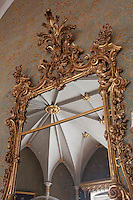 Detail of an 18th century giltwood mirror reflecting the ribbed vaulting of the gothic music room