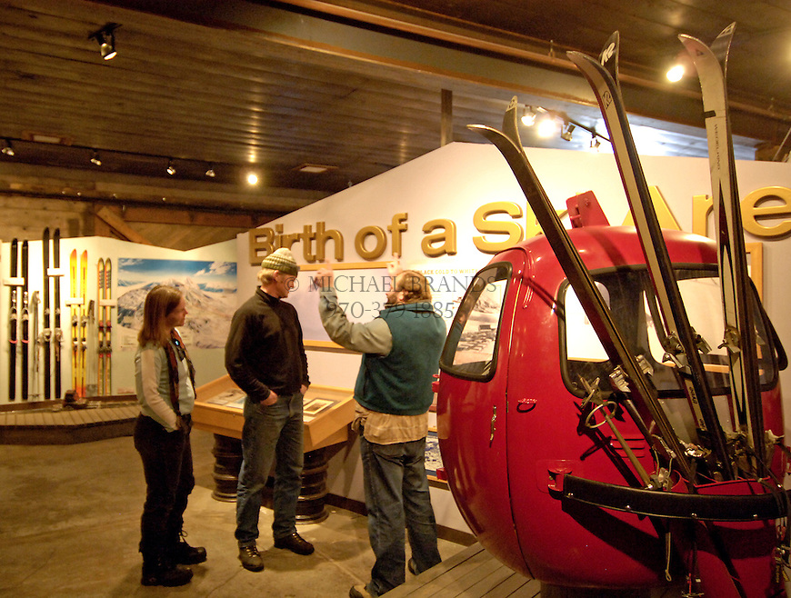 """From the left, museum docent Maria Fenerty, Andy Bamberg, and Crested Butte resident Russell Lallier talk about the early skiing days of Crested Butte at the Crested Butte Mountain Heritage Museum. Lallier, who has lived in Crested Butte his entire life, says of the original gondola car in the foreground, """"I rode this when I was a little kid."""" © Michael Brands. 970-379-1885."""