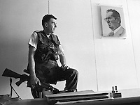 A Bosnian Army sniper armed with a Dragunov rifle looks past a portrait of the late Yugoslav leader Joseph Tito in his position in a Sarajevo office building on June 19, 1992.