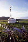 Aermotor windmill and water tank, clouds; sundown, ruts with puddles, California.