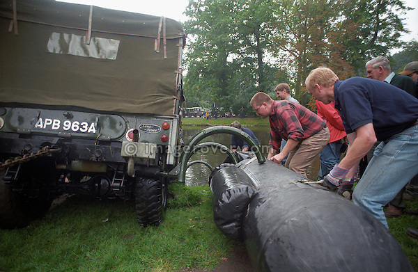 Attaching the flotation bags to a historic 1963 APGP amphibious Land Rover for a swim in a lake to commemorate Land Rovers 50th anniversary at the 1998 Belgium National show.  RELEASES MAY BE AVAILABLE FOR CERTAIN USES, PLEASE ENQUIRE. Automotive trademarks are the property of the trademark holder, authorization may be needed for some uses. --- Info: This Land Rover is known as the A.P.G.P. , Air Portable General Purpose. Based around a 1 Ton military spec 109 24 Volt, it has amphibious capabilities. This LR floats! A small propeller is mounted on te rear propshaft, the air bags were inflated from the exhaust. This was to be a multi role vehicle. The APGP can be a radio station, wombat carrier or 110 Volt power tool source and could be stacked two high for air transport. About 26 of these vehicles were built for troop trials in 1964 but never entered service. This is the first vehicle to find its way into the Dunsfold Collection, purchased in 1968 via Ruddington military auctions. In 1998 for the 50th Anniversary of Land Rover the mad idea came up to swim the APGP, which turned out to be an interesting challange as the flotation bags were by then already over 30 years old. Steering in the water is interesting as it relies on the front tyres as rudders, wind could be disastrous.