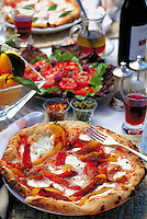 Pizzas prepared in an Italian wood burning cooking oven in a garden table setting with sliced tomatoes, lemons and wine.