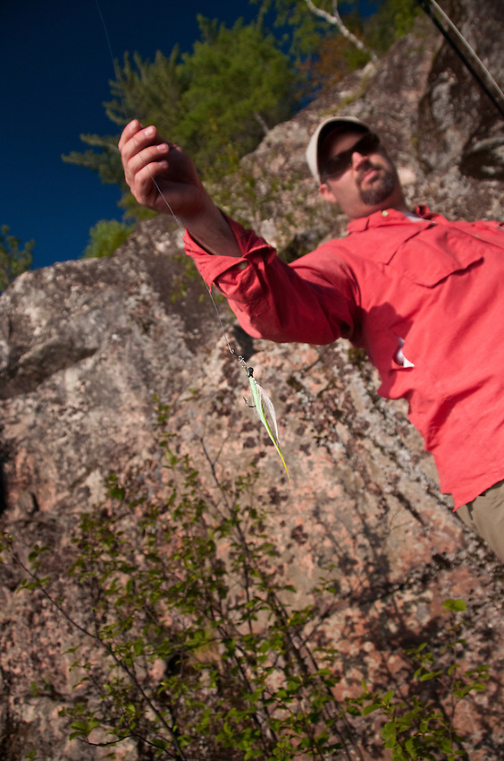 An angler displays a fly while fishing for bass pike and musky at the base of a rock cliff at Craig Lake State Park in Michigan's Upper Peninsula.