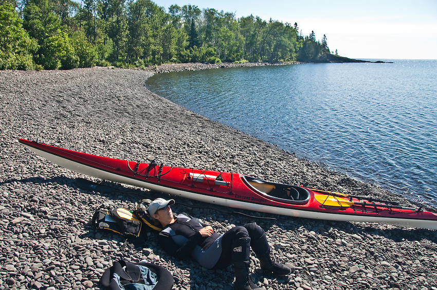 Sea kayaker resting on a beach with a red kayak.