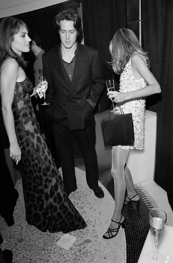Liz Hurley, Hugh Grant, and Candace Bushnell at the opening party for the Versace Versus store in New York City, 1996