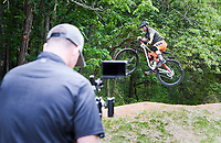 """Rich Drew (right) jumps his bike over a hill as Brock Wagner (left) films, Thursday, May 21, 2020 at Slaughter Pen bike trail in Bentonville. <br /> <br /> Rich Drew, founder of the Rider Series MTB Skills Clinic, filmed an episode of his Youtube channel, Richdrew, where he provides how-to tutorials on riding to his viewers. <br /> <br /> He started the channel in January before the pandemic sent the country into lockdown, shuttering his ride series for two months. <br /> <br /> The shutdown gave him the opportunity to pivot harder towards his channel, which started at about 1,900 viewers, ballooning to 22.6 thousand. <br /> <br /> """"It was tough for me because that was my family's main revenue source. Thankfully, they're coming back,"""" he said of his class regulars. Saturday will be his second class since jumpstarting his in-person series again.<br /> <br /> He will hold his second class, MTB 101 Fundamentals, on Saturday from 8am to noon and 1pm to 5pm at a field in Memorial Park behind the basketball courts. He said they will adhere to CDC guidelines of social distancing. Check out nwaonline.com/200522Daily/ for today's photo gallery. <br /> (NWA Democrat-Gazette/Charlie Kaijo)"""