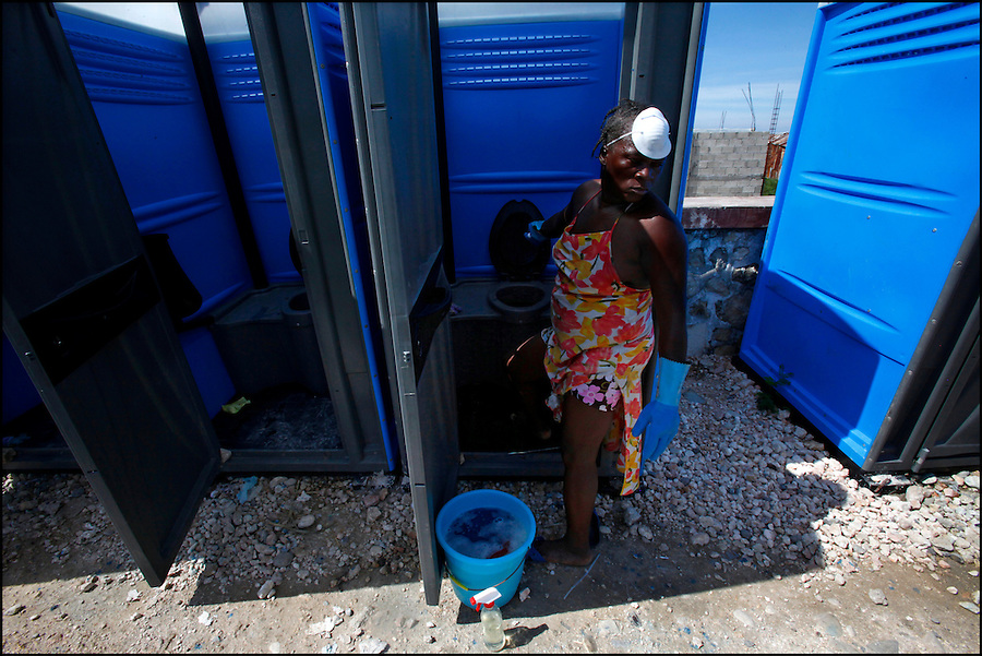 Nov 10, 2010 - Port-au-Prince, Haiti.A local resident of the Cite Soleil area of Port-au-Prince, Haiti reacts to the smell as she opens the door to a portable toilet inside a tent city to clean it on Wednesday, November 10, 2010 as fears of a Cholera outbreak spread through the area just two days after cases of the infection were confirmed in the area, the poorest slum in Haiti's capital. Officials from the Pan American Health Organization warn that Haiti's cholera epidemic, spread primarily through consuming infected water and food, is likely to grow much larger in the wake of Hurricane Tomas.  (Credit Image: Brian Blanco)