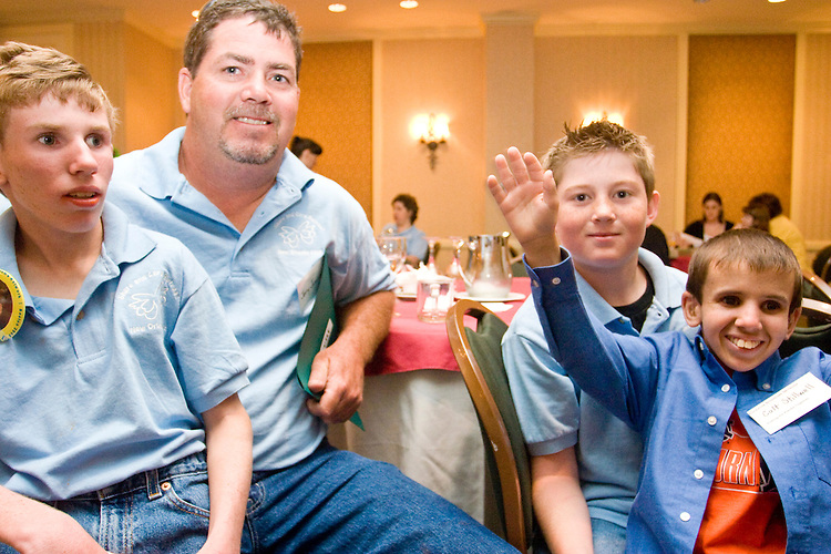 Jerry Jaminet and his sons Nicholas, left, and Austin, along with Colt Stillwell (waving) at the Share and Care Network's annual retreat held at the Doubletree Guest Suites Hotel in Boston on May 20, 2006. <br /> <br /> The Share and Care Network was created in 1981 by Pat Cahill when her son Scott was diagnosed with Cockayne Syndrome.  A rare form of dwarfism, Cockayne Syndrome is a genetically determined condition whose symptoms include microcephaly, mental retardation, progressive blindness, progressive hearing loss, premature aging, and a shortened lifespan averaging 18 years.  Those afflicted have distinctive facial features, including sunken eyes, pinched faces, and protruding jaws as well as distinctive gregarious, affectionate personalities.<br /> <br /> Because of the rarity of the condition (1/1,000 live births) and its late onset (characteristics usually begin to appear only after one year), many families and physicians are often baffled by children whose health begins to deteriorate after normal development.  It was partly with this in mind that the Share and Care Network was formed, to promote awareness of this disease as well as to provide a support network for those families affected.  In 1998 it began organizing an annual retreat, which has grown from three families in its inaugural year to more than 30 today.  Although the retreat takes place in the United States, families from as far as Japan arrive for this one weekend out of the year to share information and to support one another.