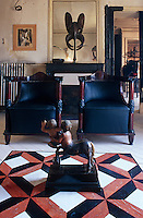 A wooden statue of a centaur sits on a marble inlaid table facing a pair of Empire armchairs in the living room