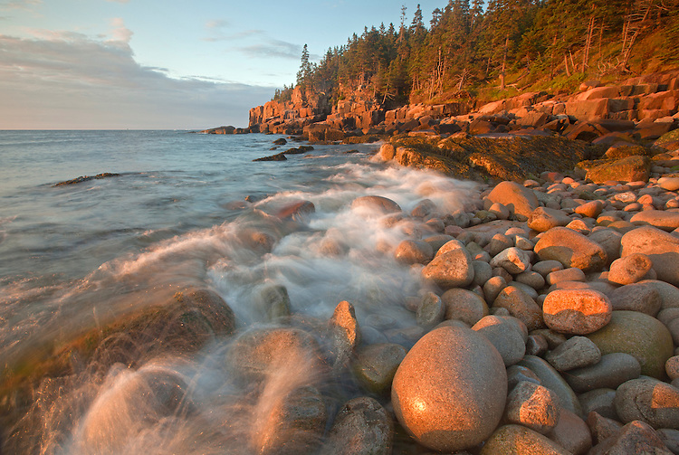 Waves splash against granite boulders at Boulder Beach and the Otter Cliffs, Acadia National Park, Maine, USA