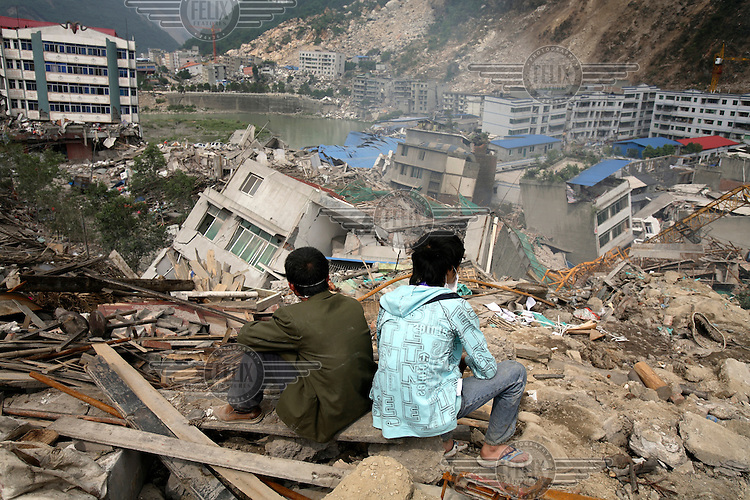 Residents look out over a landscape of collapsed buildings. An earthquake measuring 7.9 on the richter scale hit Sichuan on 12/05/2008.