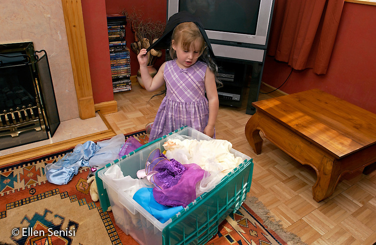 MR / Radley, Abingdon, Oxfordshire, England.Girl (5) looks through box of dress-up clothes in her living room..MR: Web4.©Ellen B. Senisi