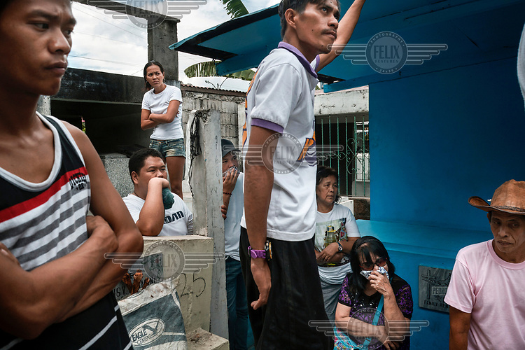 Family and friends watch as a coffin is interred during a funeral in Manila North Cemetery. Manila North Cemetery is home to thousands of 'informal settlers' who have built shacks using in and around the mausoleums, crypts and tombs. In comparison to the city's dangerous shantytowns the cemetery is relatively quiet and safe. However, water must be collected from a few public wells and the electricity supply is erratic, usually stolen from mains cables. In the summer the sweltering heat drives people to sleep outside often on top of the tombs.<br /> <br /> Some of the residents live in the crypts and mausoleums of wealthy families, who pay them a stipend to clean and watch over them. Others make a living carving headstones or selling candles to visitors and helping out at funerals as the daily life of the cemetery goes on around the people who live there.