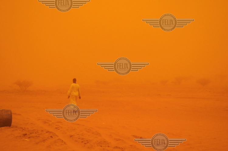 A man walks through a severe dust storm (known as a Haboub) in the desert of Eastern Sudan.